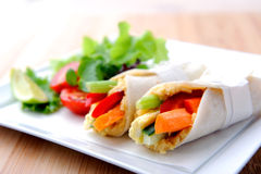 Healthy bite size wraps with carrot, capsicum and a side salad. Mini tortilla wraps with raw vegetable sticks Royalty Free Stock Image