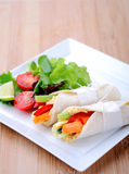Healthy bite size wraps with carrot, capsicum and a side salad. Mini tortilla wraps with raw vegetable sticks Royalty Free Stock Photos