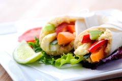 Healthy bite size wraps with carrot, capsicum and a side salad. Mini tortilla wraps with raw vegetable sticks Royalty Free Stock Photography