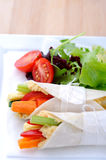 Healthy bite size wraps with carrot, capsicum and a side salad. Overhead of mini tortilla wraps with raw vegetable sticks Royalty Free Stock Photo