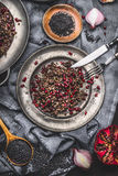 Healthy Black beluga lentil salad with pomegranate in metal plate with cutlery on dark rustic background with cooking ingredients Stock Photo