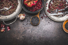 Healthy Black beluga lentil salad preparation with pomegranate on dark rustic background, top view Royalty Free Stock Photo