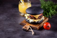 Healthy black burger with beef, iceberg salad, slice of tomato and toast cheese. Healthy food. Royalty Free Stock Image