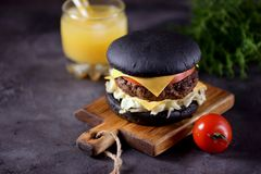 Healthy black burger with beef, iceberg salad, slice of tomato and toast cheese. Healthy food. Royalty Free Stock Photo