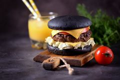 Healthy black burger with beef, iceberg salad, slice of tomato and toast cheese. Healthy food. Stock Photography