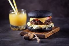 Healthy black burger with beef, iceberg salad, slice of tomato and toast cheese. Healthy food. Stock Images