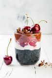 Healthy Black Forest dessert. Black activated charcoal chia pudding with cherries, coconut cream and chocolate. Vegan breakfast Royalty Free Stock Photos