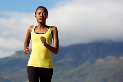 Healthy black woman running outdoors in nature. Portrait of healthy young black woman running outdoors in nature Stock Photography