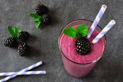 Blackberry smoothie close up, downward view against a dark background. Healthy blackberry smoothie in a glass. Close up, downward view against a dark slate stock photos
