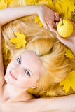 Healthy blonde girl on a diet. Over yellow leaves stock image