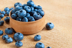 Healthy blueberries in bowl on wooden background. Stock Image