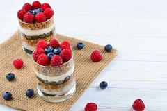 Healthy blueberry and raspberry parfait in a glass on a rustic w. Hite wood background. Two portions. Space for text or design royalty free stock photography