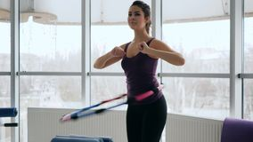 Healthy body, slim female performs exercise with plastic ring against of large windows stock footage