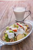 Healthy bowl of muesli, apple, fruit, nuts and milk for a nutrit Royalty Free Stock Photography