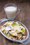 Healthy bowl of muesli, apple, fruit, nuts and milk for a nutrit Stock Photo