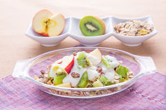 Healthy bowl of muesli, apple, fruit, nuts and milk for a nutrit Stock Image