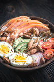 Healthy bowl with salmon, avocado, egg and vegs Stock Photo