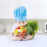 Healthy boy chef with vegetable at home Royalty Free Stock Photos