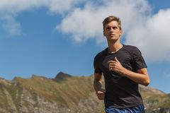 Young man running in the mountains during a sunny day stock photo