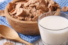Healthy bran flakes in a wooden bowl and milk close-up. horizont Stock Photos