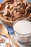 Healthy bran flakes in a wooden bowl and milk close-up. Vertical Stock Photography