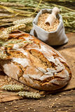 Healthy bread and a bag with grains Stock Photos