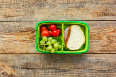 Healthy break with cherry, grape and sandwich in lunchbox on home table flat lay Stock Image