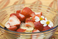 Healthy Breakfast. Food for Breakfast A bowl of strawberries and bananas with muesli.They're on an Indian style table cloth with some white flowers royalty free stock image
