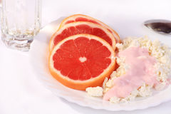 Healthy breakfast. Healthy breakfast of grapefruit and cottage cheese on a white background Royalty Free Stock Photo