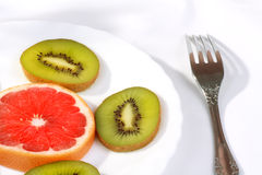 Healthy breakfast. Slices of fruit on white background \ sliced kiwi fruit, citrus, on a white plate and lying next to the fork Stock Photo