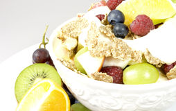 Healthy breakfast. White bowl with mixed fruits, corn flakes and yogurt decorated with a kiwi half, an orange and grapes on the side Royalty Free Stock Image