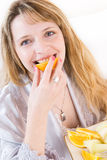 A healthy breakfast. A blond woman biting a slice of orange Royalty Free Stock Image