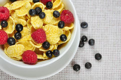 Healthy breakfast. Corn flakes, raspberry and  blueberry in white bowl close up Stock Photos