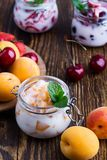 Healthy breakfast with apricot yogurt and fresh summer fruits. Sweet cherry, lime and strawberry on rural table royalty free stock image