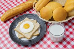 Healthy breakfast with assorted breads on the table. Top view of fried egg and wheat breads on the plate with assorted fresh breads above dining table Royalty Free Stock Photo