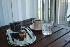 Healthy breakfast on the balcony. Cup of coffee, cookies on shiny plate, glass of pure water and blueberries on wooden table. royalty free stock image