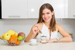 Healthy breakfast. Beautiful woman having coffee, fruits and oatmeal for breakfast Stock Photography
