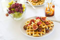 Healthy breakfast: Belgian waffles with figs, grapes and caramel Stock Photos