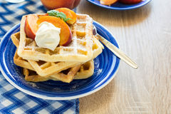 Healthy breakfast: Belgian waffles with peach slices and cream decorated mint leaves and blue napkin Royalty Free Stock Image