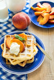 Healthy breakfast: Belgian waffles with peach slices and cream decorated mint leaves and blue napkin Royalty Free Stock Photography