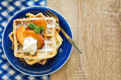 Healthy breakfast: Belgian waffles with peach slices and cream decorated mint leaves and blue napkin Royalty Free Stock Images