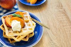 Healthy breakfast: Belgian waffles with peach slices and cream decorated mint leaves and blue napkin Stock Images
