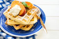 Healthy breakfast: Belgian waffles with peach slices and cream decorated mint leaves and blue napkin Royalty Free Stock Photos