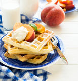 Healthy breakfast: Belgian waffles with peach slices and cream decorated mint leaves and blue napkin Stock Image