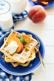 Healthy breakfast: Belgian waffles with peach slices and cream decorated mint leaves and blue napkin Stock Photography