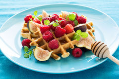 Healthy breakfast: Belgian waffles with raspberries, honey and figs decorated mint leaves on turquoise napkin Royalty Free Stock Photos