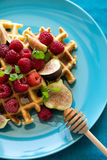 Healthy breakfast: Belgian waffles with raspberries, honey and figs decorated mint leaves on turquoise napkin Stock Image