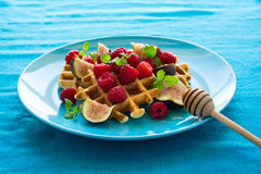 Healthy breakfast: Belgian waffles with raspberries, honey and figs decorated mint leaves on turquoise napkin Royalty Free Stock Photography