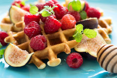 Healthy breakfast: Belgian waffles with raspberries, honey and figs decorated mint leaves on turquoise napkin Stock Photos
