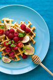 Healthy breakfast: Belgian waffles with raspberries, honey and figs decorated mint leaves on turquoise napkin Royalty Free Stock Photo